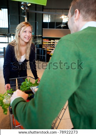 A woman riding on a grocery cart being pushed by a man - stock photo