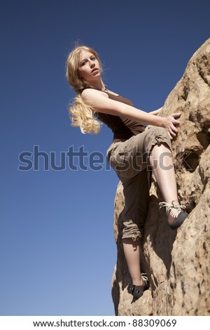 A woman rock climbing looking down at the ground. - stock photo