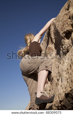 A woman rock climbing looking up in the sky. - stock photo