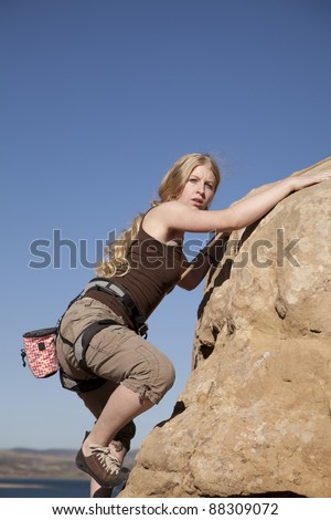 A woman rock climbing with a  serious expression. - stock photo