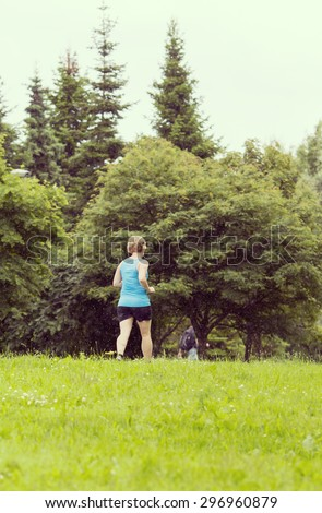 A woman running in the rain. Image has a vintage effect. - stock photo