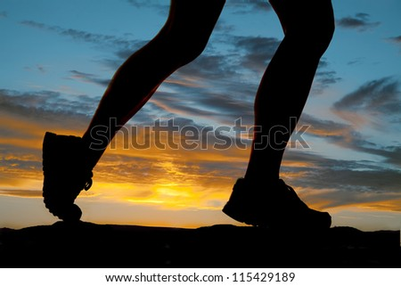 A woman running in the sunset legs silhouette. - stock photo