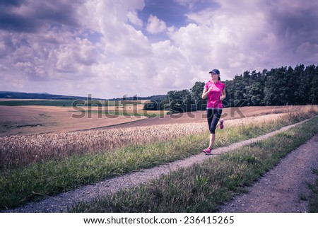 a woman running through the rural landscape - stock photo