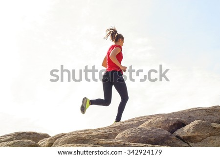 A woman running up a hill - stock photo