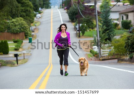 A woman runs with her golden retriever dog on the street - stock photo