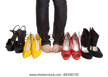 A woman's feet surrounded by a bunch of shoes.
