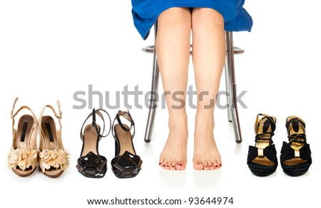 A woman's feet surrounded by a bunch of shoes. - stock photo
