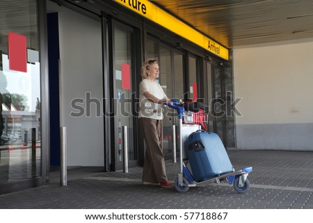 a woman's going out from the airport  with a  trolley - stock photo