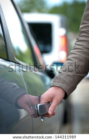 A woman's hand about to open the door of a modern vehicle.