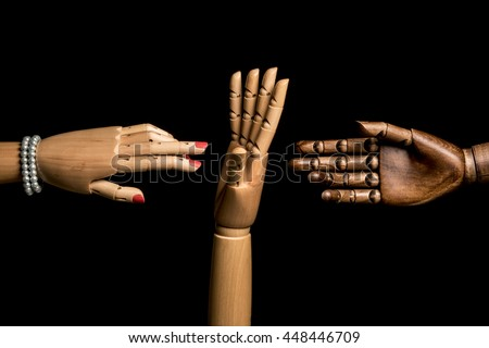 A woman's hand and one hand of black man meet. A white hand opposes. On black background. With copy text. - stock photo