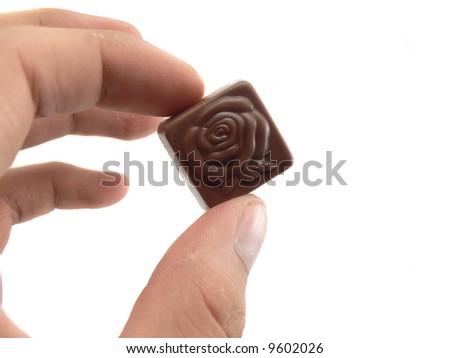 A woman's hand choosing a chocolate - stock photo