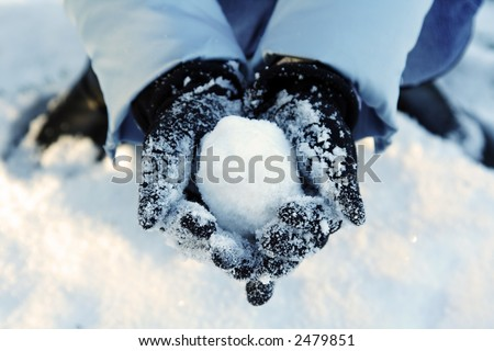 A woman's hand holding a snowball - stock photo