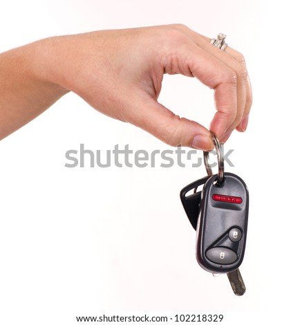A woman's hand holds car keys key-chain with electronic door opener in fingertips