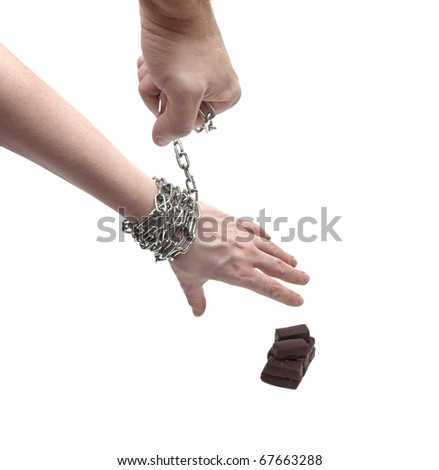 a woman's hand reaching for a chocolate candy - stock photo