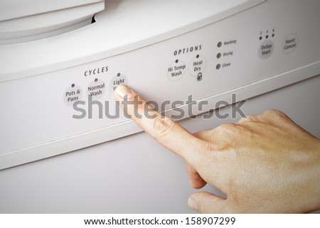 A woman's hand setting the dishwasher cycle to light wash, energy efficient concept - stock photo