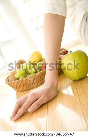 A woman's hand with a fruit basket and an apple