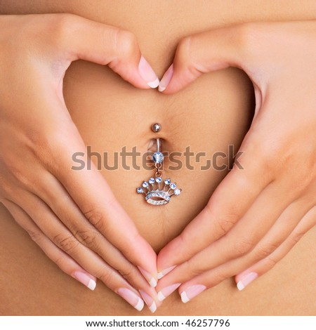 A woman's hands forming a heart symbol around navel with piercing - stock photo