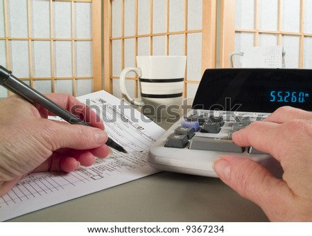 A woman's hands holding a pen and working with a tax form and adding machine.