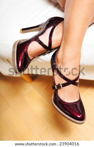 A woman's legs in cherry red  patent leather high heel shoes - stock photo