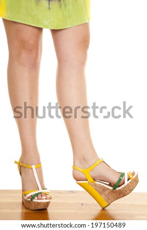 a woman's legs in her shoes while wearing a dress. - stock photo
