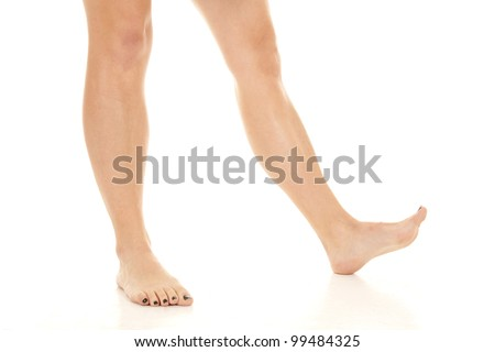 A woman's legs standing and walking on the floor without shoes. - stock photo