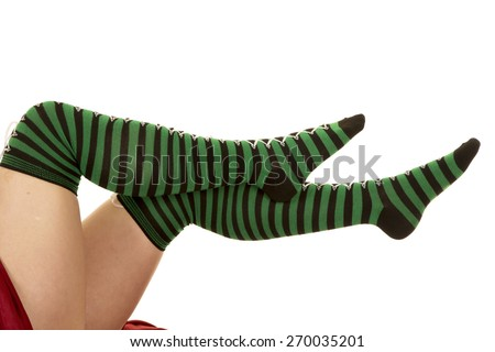 a woman's legs up in the air, with her green and black stockings on. - stock photo