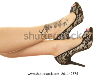 A woman's legs up, with her tattoo and lace shoes. - stock photo