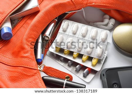 A woman's purse and pills and accessories - stock photo