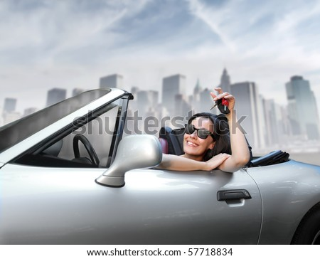 a woman's showing a key sitting on an expensive car - stock photo