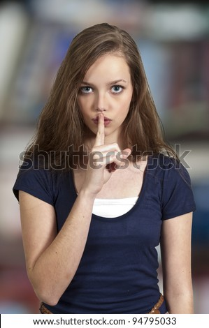 A woman saying be quiet by saying shhh - stock photo
