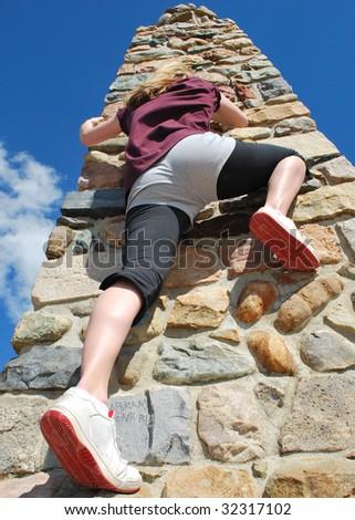A woman scaling a rock pillar. - stock photo