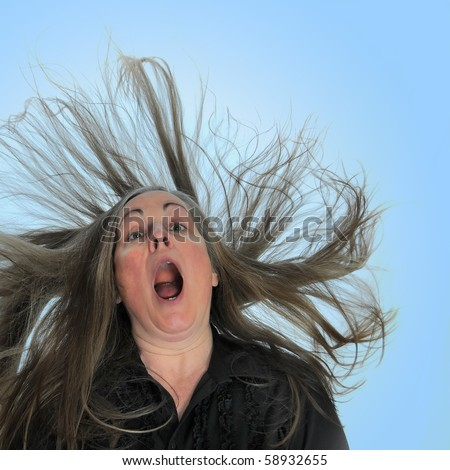 A woman screaming in front of a blue background with her hair blasting behind her. - stock photo