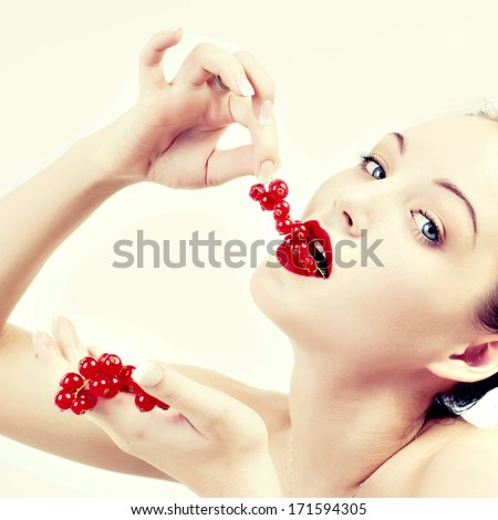 A woman seductively eating red berries.  - stock photo