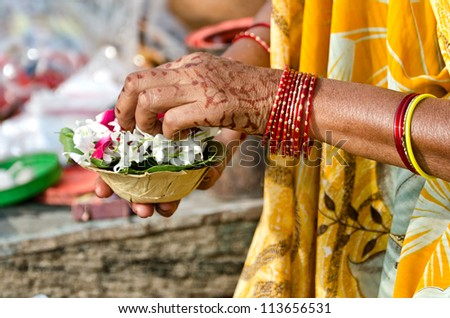 A woman sets the candle and the flowers for the morning rituals to Ganges - stock photo