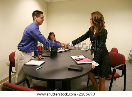 A woman shaking a mans hand to conclude a business deal - stock photo