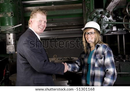 A woman shop worker shaking hands with her boss who is pleased with her work.