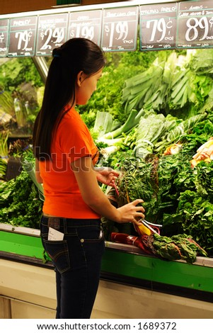 A woman shopping at produce section of grocery store - stock photo