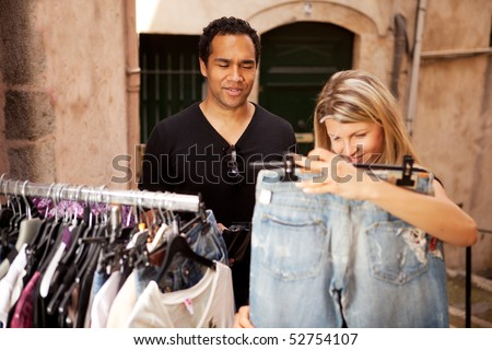 A woman shopping for expensive clothes, shallow depth of field - focus on man - stock photo