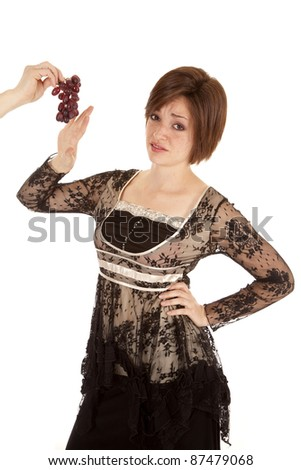 A woman showing her face of displeasure because she does not want the grapes.