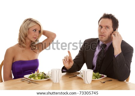 A woman showing her frustration with her man while they are having a fancy dinner he is on the phone telling her to hang on a minute. - stock photo