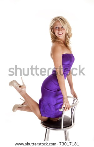A woman showing her fun side by kicking up her feet on a stool in her beautiful purple dress.