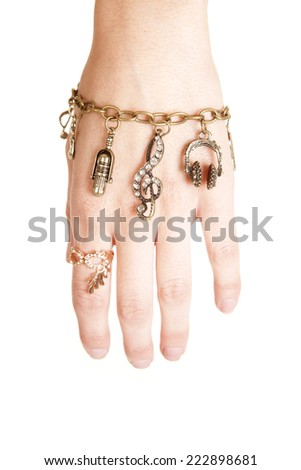 A woman showing her hand, with a bracelet with charms hanging from them. - stock photo