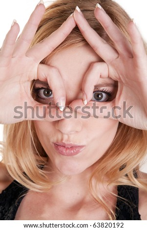 A woman showing her silly side by putting her fingers over her eyes. - stock photo