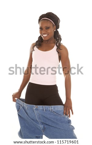 A woman showing off her healthy life by holding out her big pants. - stock photo