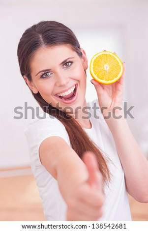 A woman shows an orange, thumbs up