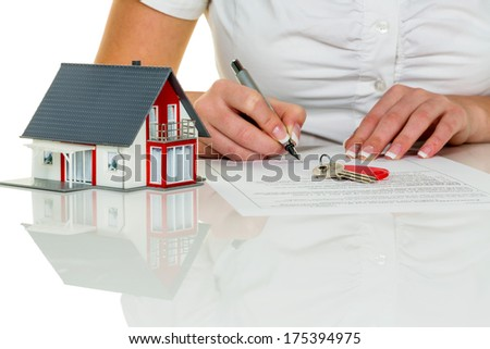 a woman signs a contract to purchase a home with a real estate agent. - stock photo