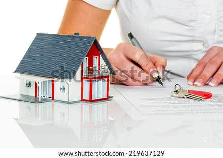 a woman signs a purchase agreement for a house in a real estate agent. - stock photo
