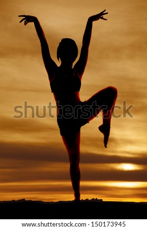 A woman silhouetted with one leg and arms up. - stock photo