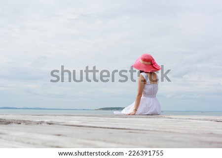 A woman sit beside the sea - stock photo