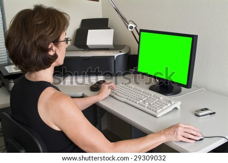 A woman siting at a desk working on her PC with green screen on the flat screen monitor. - stock photo
